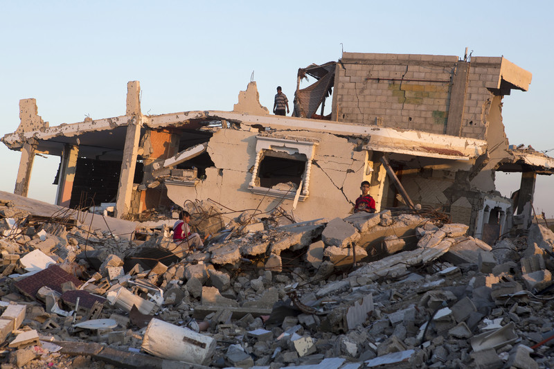 Boys sit on top of rubble in front of destroyed Gaza home