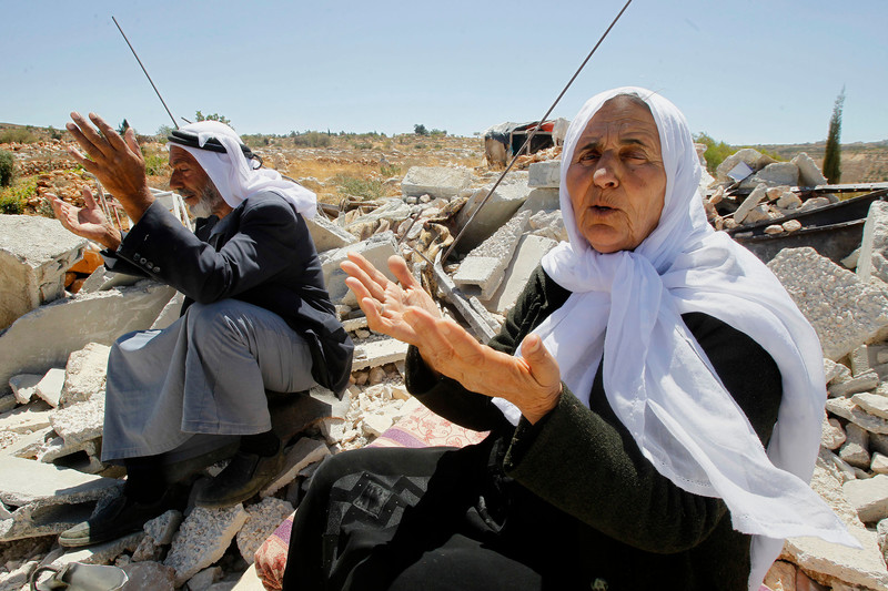 Elderly couple gesture with their hands while sitting on rubble of destroyed home