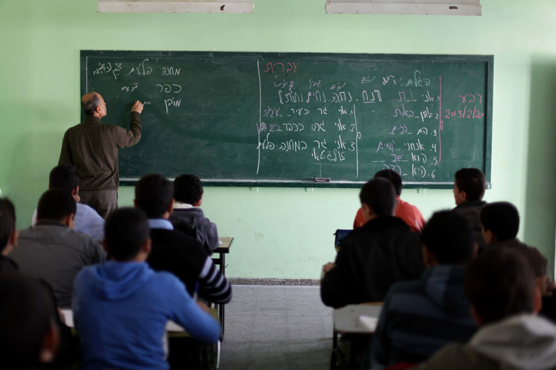 Man writes words in Hebrew on chalkboard in front of students sitting at desks
