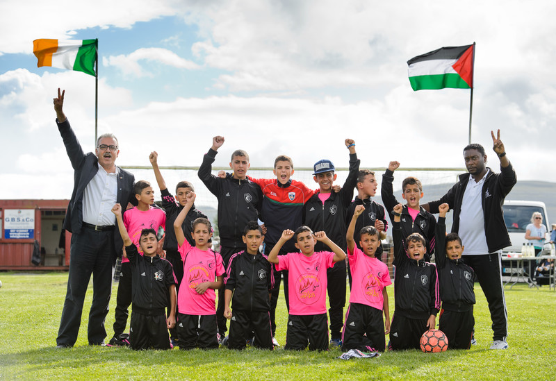 Boys in football jerseys pose with their fists in the air in front of the flags of Ireland and Palestine
