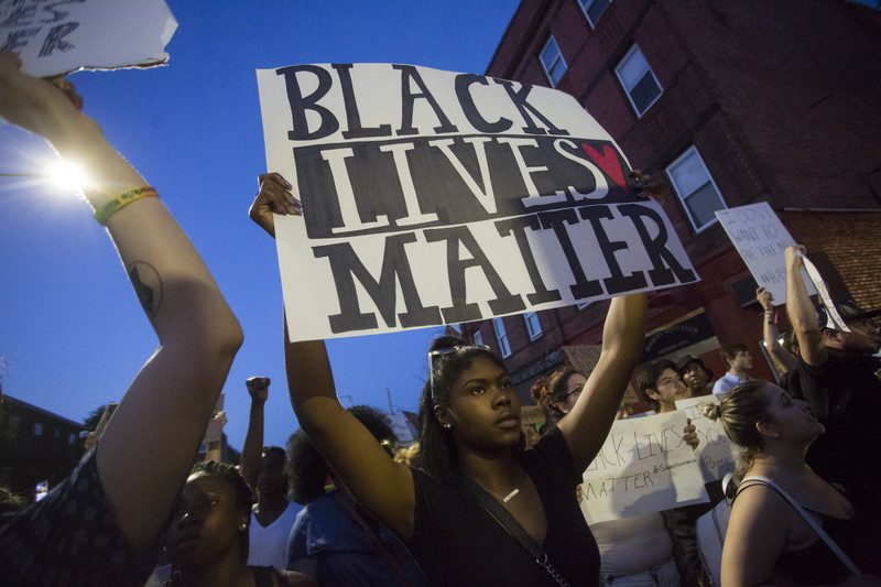 Woman holds sign reading Black Lives Matter during demonstration