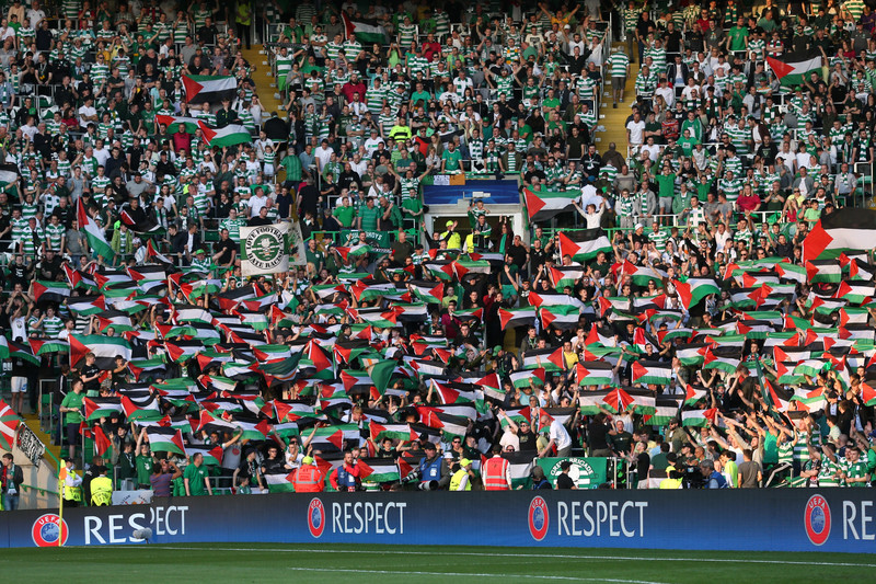 Dozens of football spectators hold up Palestinian flags in full stadium