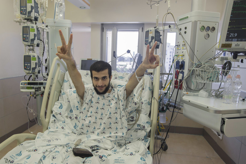 Smiling man in hospital bed raises his arms with his fingers in V for victory sign