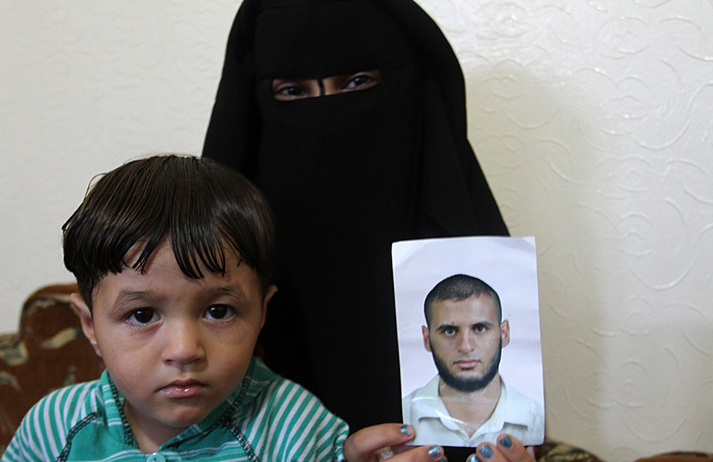Woman wearing full face covering holds photo of young man as a child sits next to her