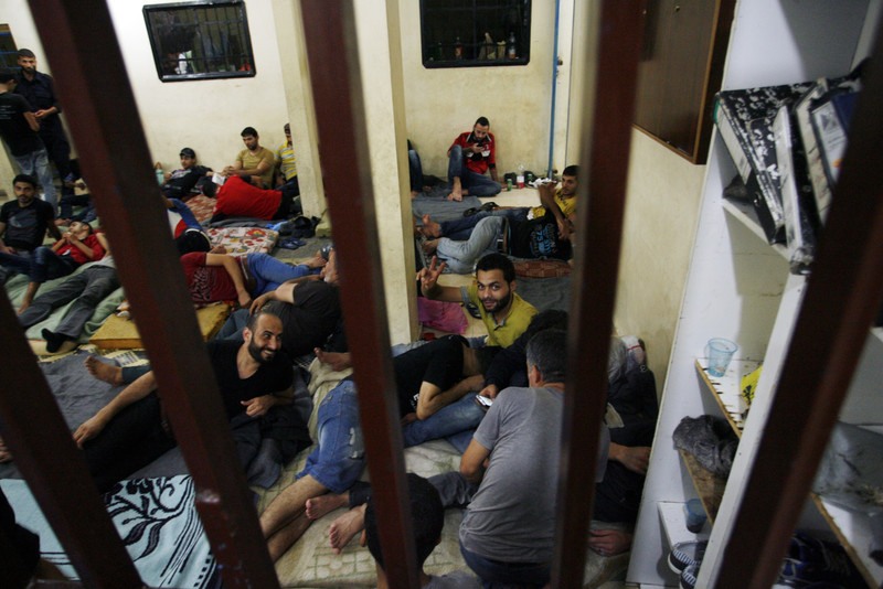 Group of men lounge on floor of detention cell