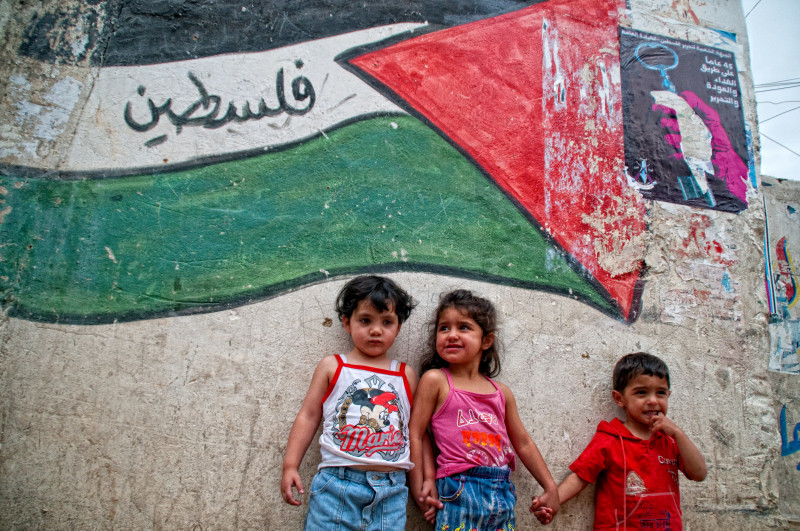 Small children stand against wall with mural of Palestine flag