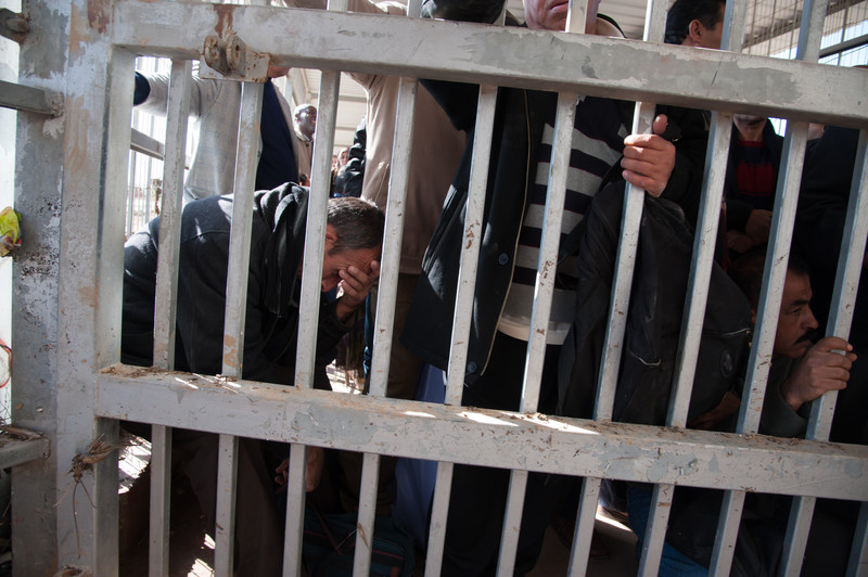 Crowd of men stand or sit behind metal bars at checkpoint