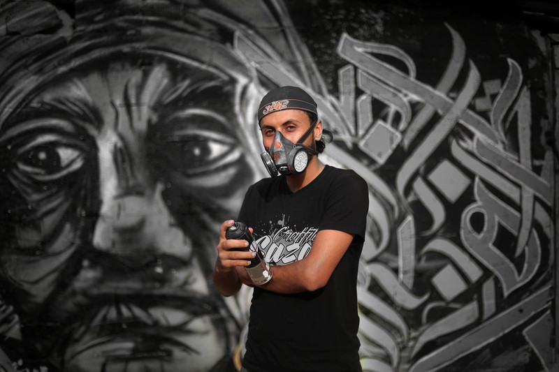 Young man wears baseball cap, gas mask and T-shirt reading Gaza graffiti while holding spray can in front of mural