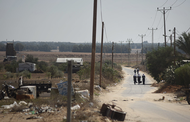 Landscape view of schoolgirls walking along road with Israeli militarized fence in distance