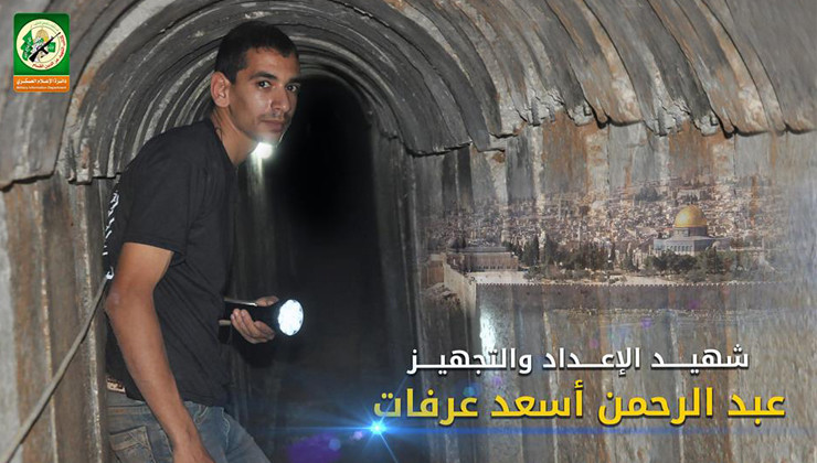 Young man holding flashlight stands in tunnel