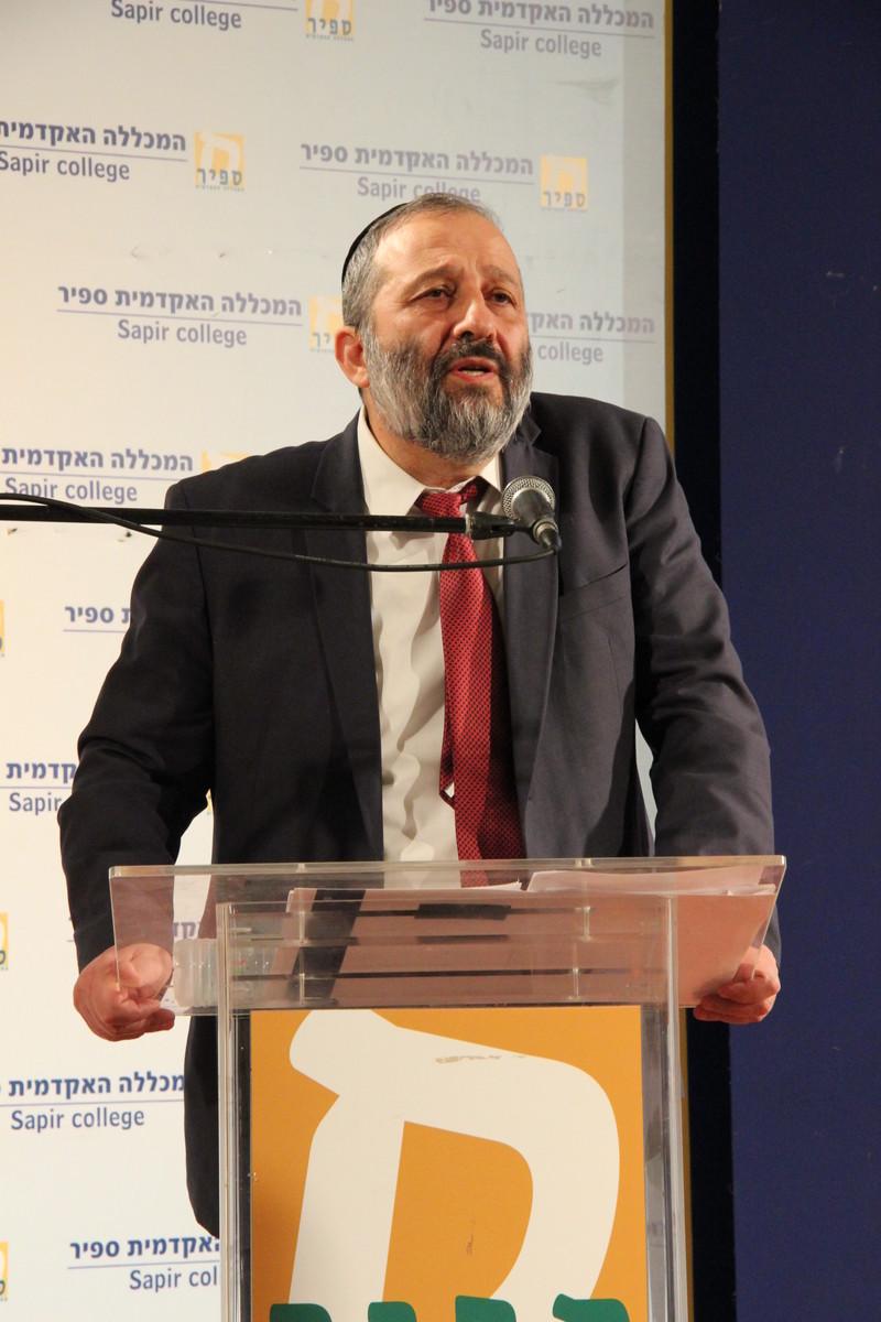 Aryeh Deri speaks at a podium