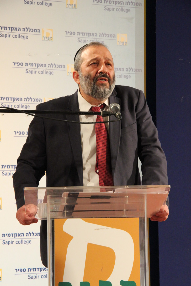 Aryeh Deri speaks at a podium