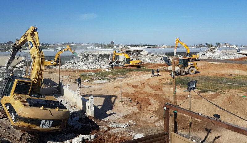 Landscape view of Caterpillar machines demolishing several homes