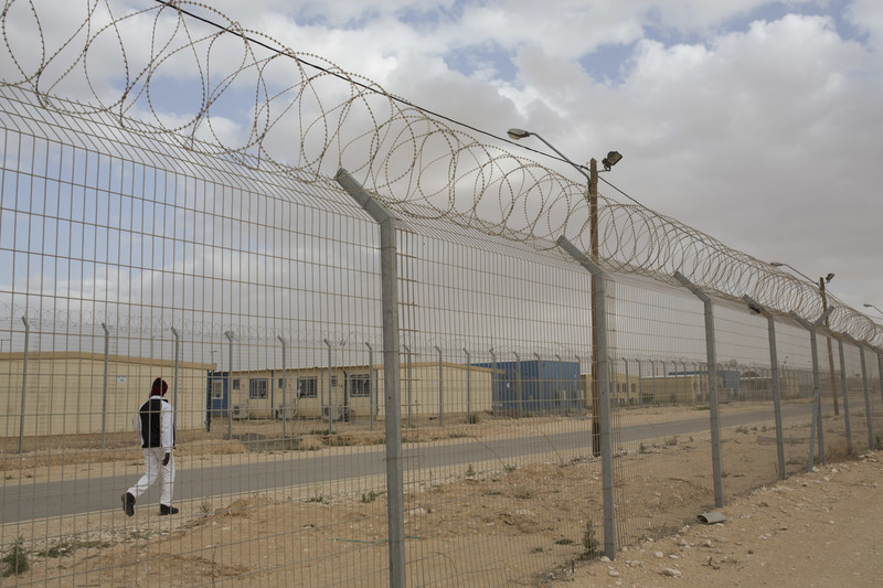 Man walks in between barracks and barbed wire fencing