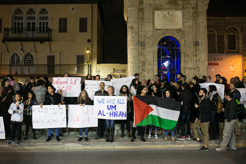 Protesters hold Palestinian flag and signs