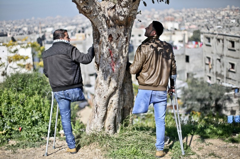 Two young men, each standing on one leg, next to tree on hill overlooking city