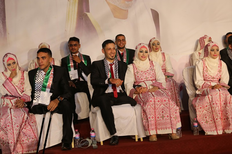 Young women wearing traditional embroidered dresses sit next to young men wearing suits
