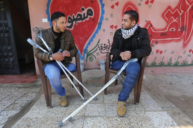 Young men holding crutches sit next to each other, smiling