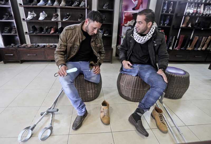 Two young men try on same pair of shoe at store