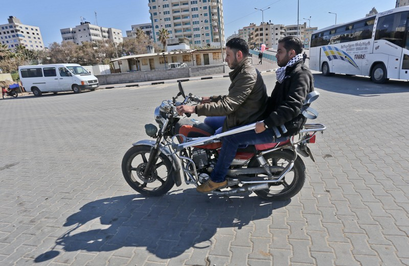 Two young men sit on motorcycle