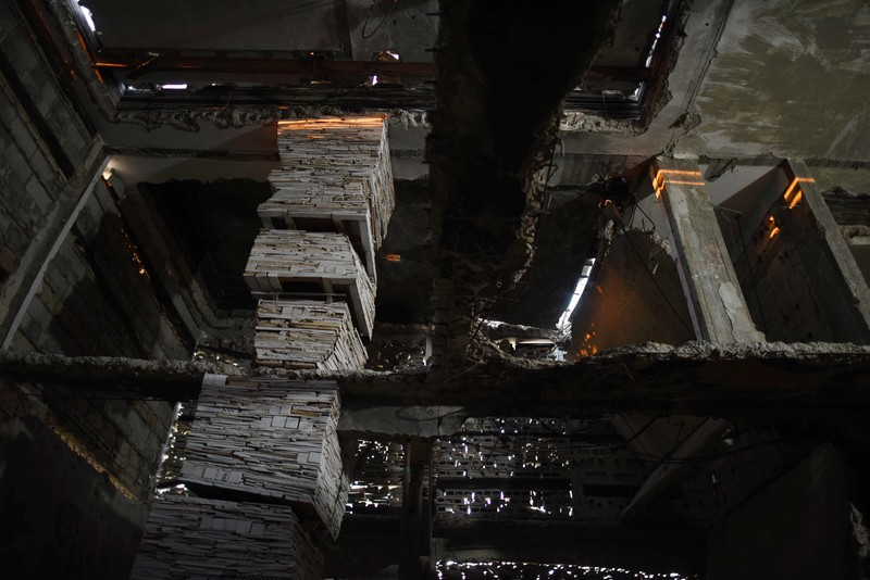 Interior view of installation shows pillars and walls made out of stacked debris