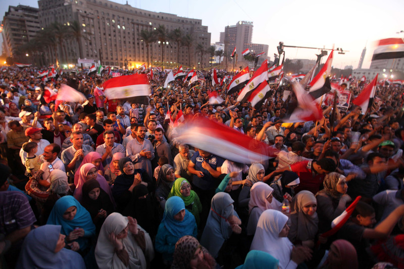 Crowd of dozens of men and women waving Egyptian flags