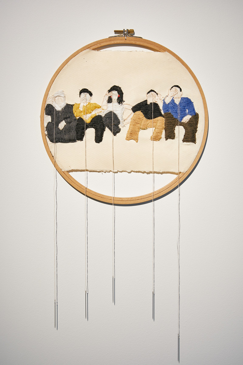 Embroidered panel framed by embroidery hoop shows five seated figures with a threaded needle hanging from each