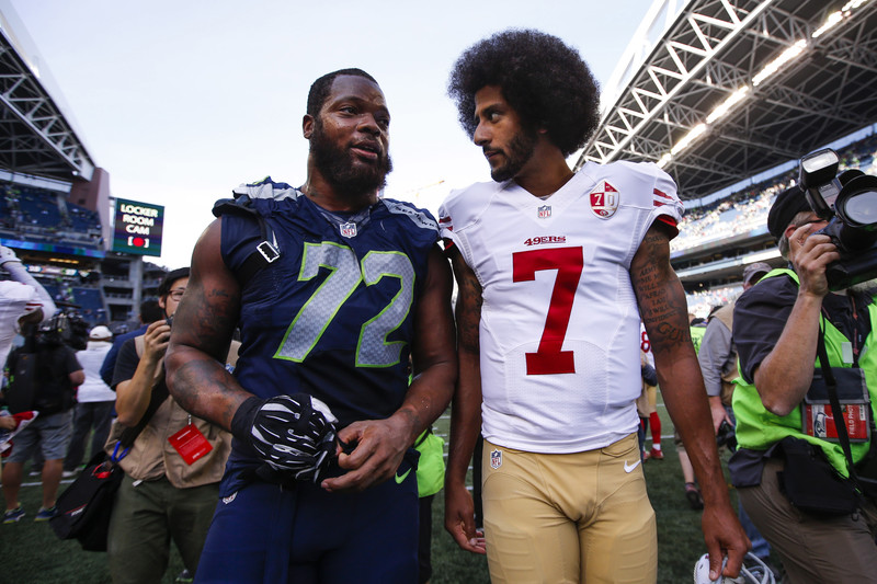 Seattle Seahawks defensive end Michael Bennett, left, talks to San Francisco 49ers quarterback Colin Kaepernick, following a 37-18 Seattle victory at CenturyLink Field in Seattle, 25 September 2016. In solidarity with Palestinians, Bennett this week pulled out of an Israeli-government backed propaganda junket for NFL players.