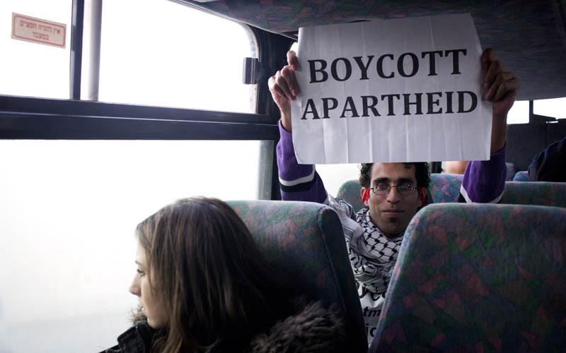 Basil al-Araj sits on bus behind Israeli woman while holding up a sign reading Boycott Apartheid
