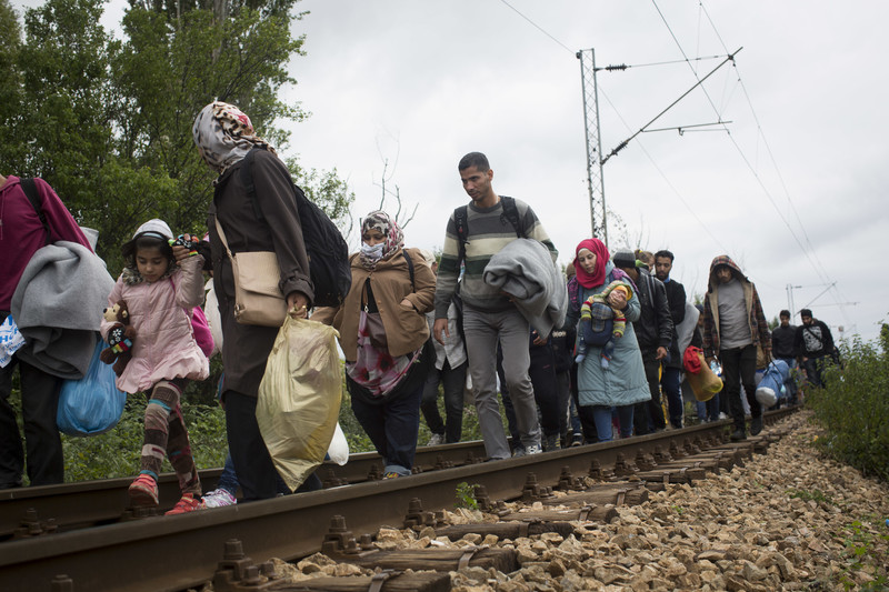 Men, women and children walk along railroad tracks while carrying their belongings