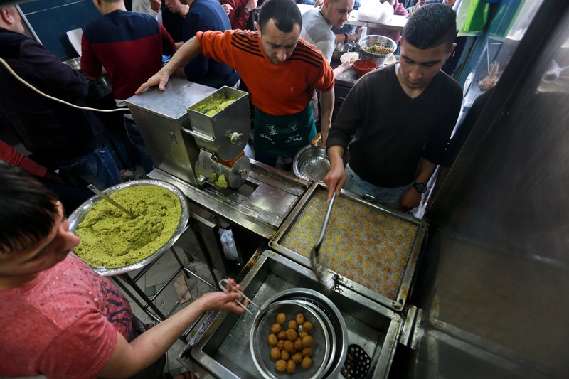Aerial view of three men working at falafel frying station