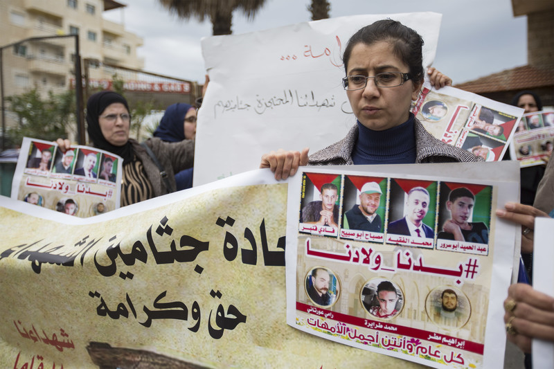 A woman holds a banner and a poster showing photos of slain men whose bodies are being held by Israel