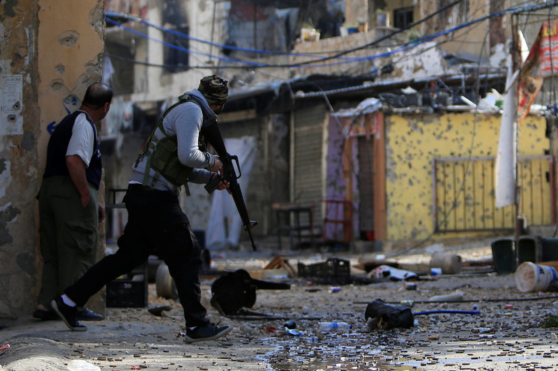 Man carrying rifle and unarmed man look around a corner in a bullet-strewn, narrow street in Ein al-Hilweh