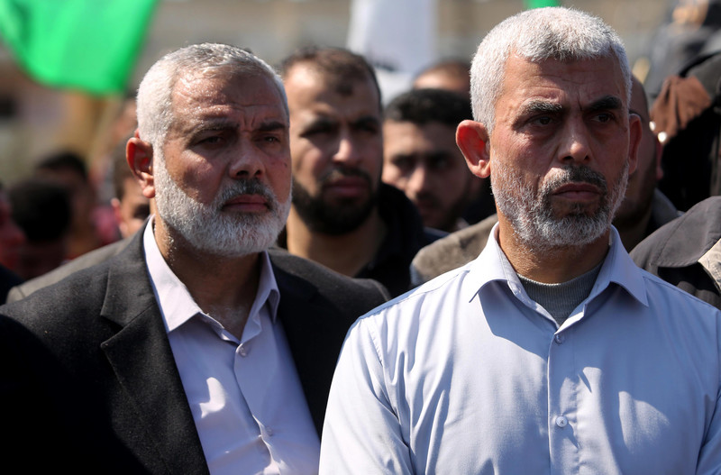 Ismail Haniyeh and Yahnya Sinwar are seen from chest up standing next to each other during Mazen al-Fuqaha's funeral