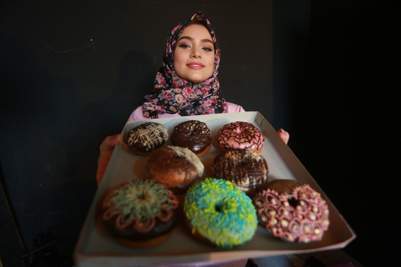Young woman holds up a tray of doughnuts with varying toppings