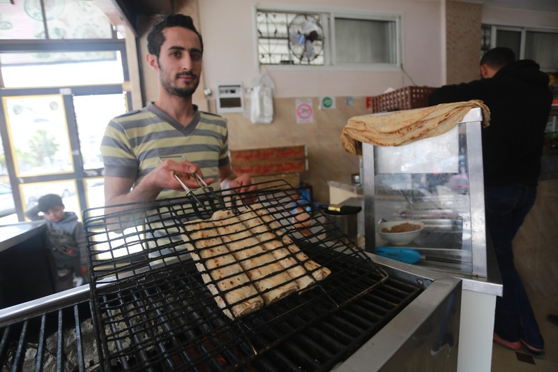 Man holds up grill press holding several falafel sandwiches