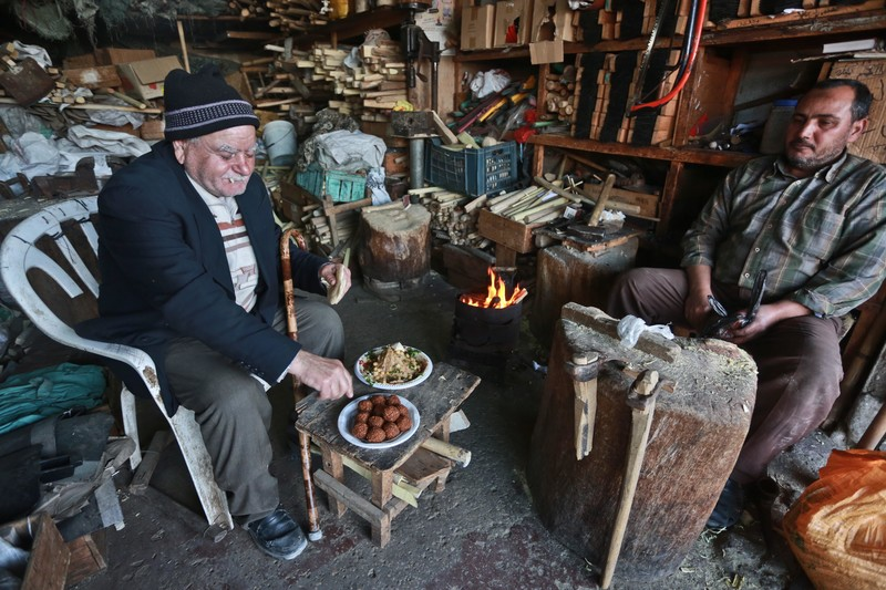 Elderly man sits on chair next to table holding small dishes of food in shop filled with wood