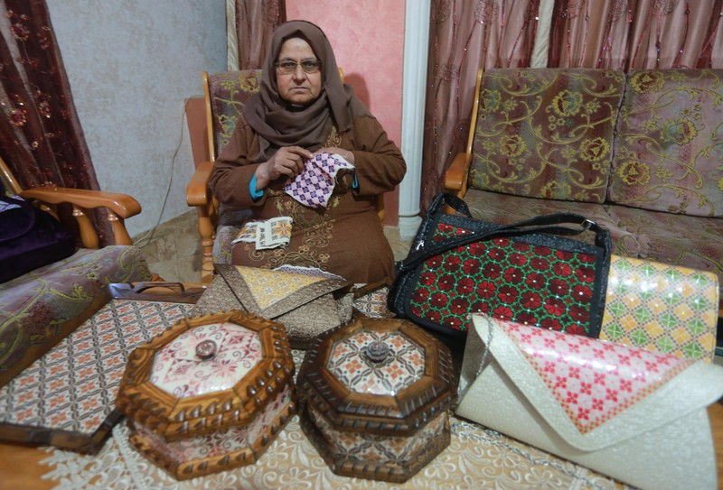 Older woman sits in chair and works on embroidery panel while surrounded by boxes and handbags decorated with embroidery