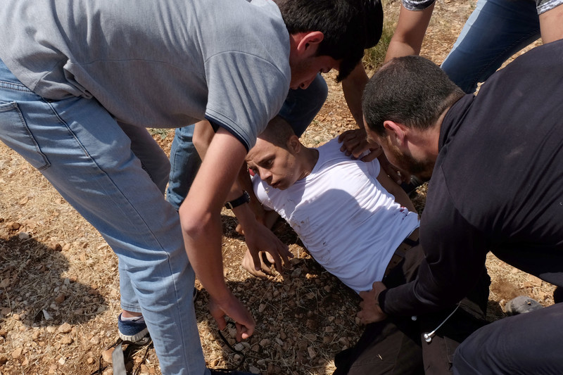 Group of youths come to aid of young man who is injured in the ground