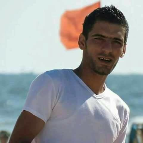 Young man in t-shirt is seen from chest up standing in front of sea