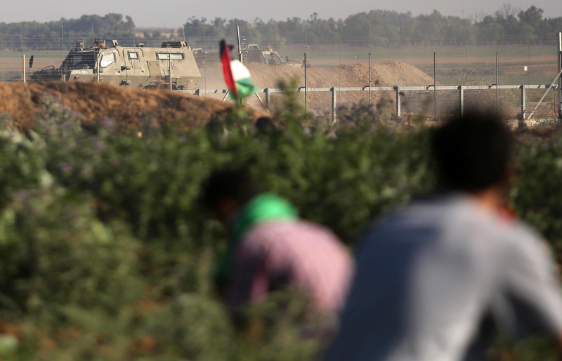 Photo shows backs of youths crouching in agricultural field, one holding a Palestinian flag, with an Israeli military vehicle in the background