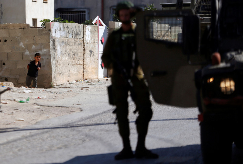 A small Palestinian boy peers behind a wall as heavily armed soldiers stand in village street