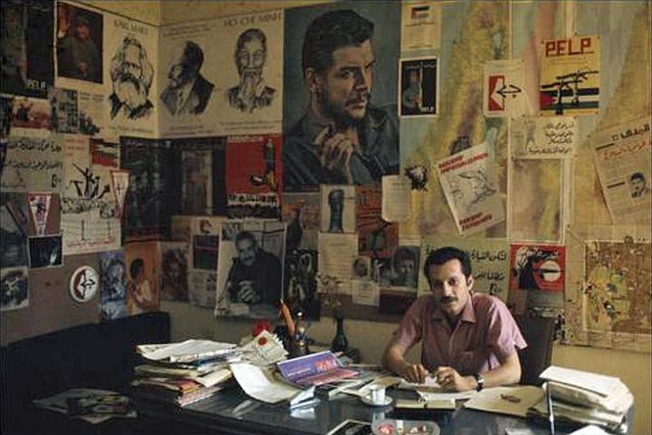Ghassan Kanafani at his desk, behind him are political posters and fliers