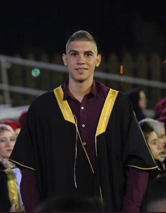 Photo shows smiling young man wearing graduation ceremony gown from waist up