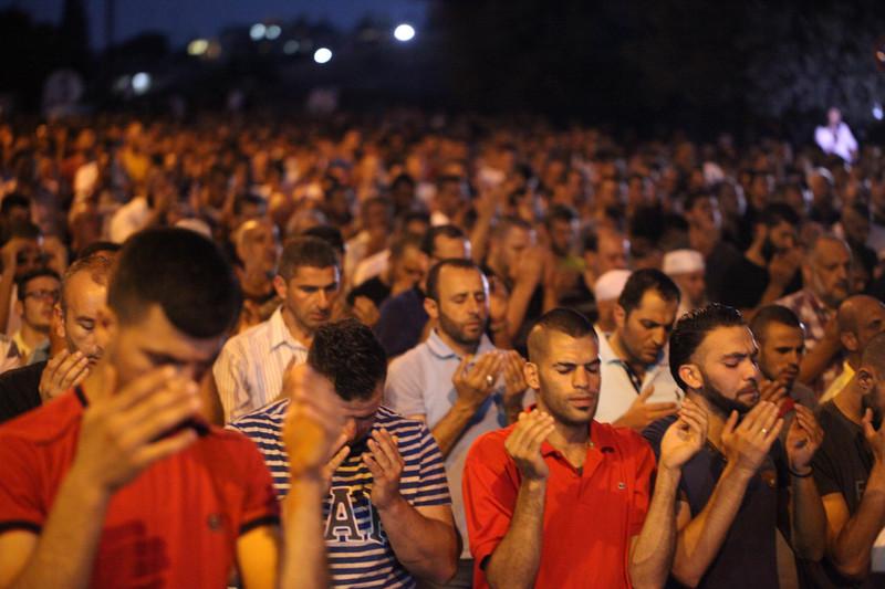 Hundreds of men pray outside at night