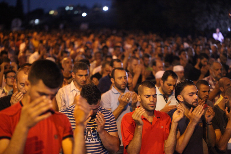 Hundreds of men pray outside at night