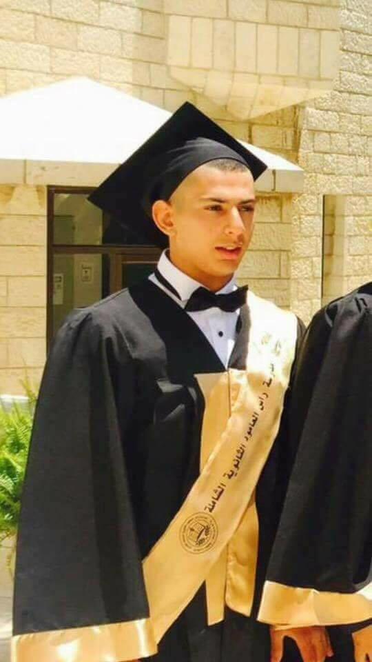 Photo shows young man wearing graduation cap and gown from waist up