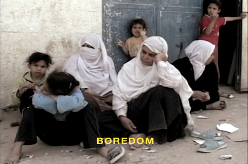 Three women sit on ground, accompanied by several children, with subtitle reading BOREDOM