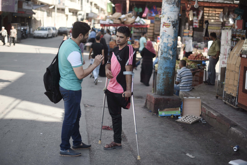 Two young men, one using arm braces, speak to each other in a marketplace