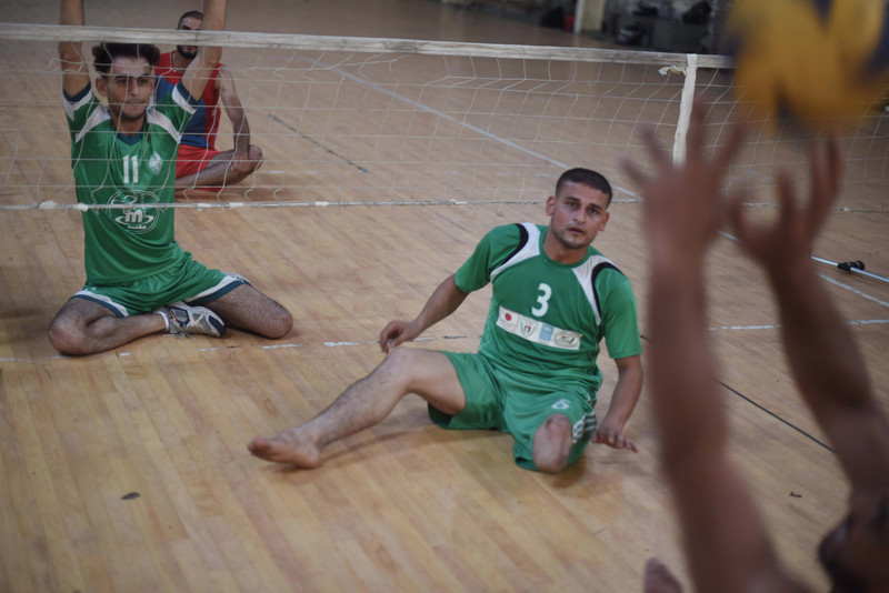 Young man wearing sports jersey sits on the ground behind a volley ball net, watching for the ball to be served